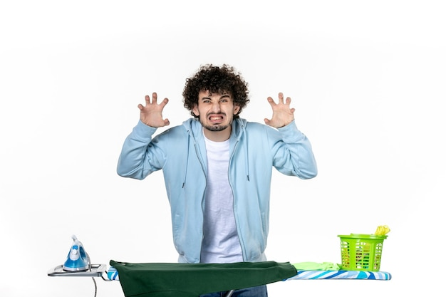 Vista frontale giovane maschio dietro l'asse da stiro arrabbiato su sfondo bianco lavanderia lavori domestici emozione colore ferro umano pulizia vestiti