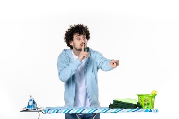 Vista frontale giovane maschio dietro l'asse da stiro chiedendo di tacere su sfondo bianco vestiti uomo lavanderia foto pulizia ferro lavori domestici color