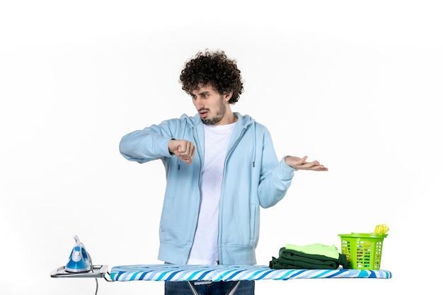 Vista frontale giovane maschio dietro asse da stiro controllo del tempo su sfondo bianco lavori domestici lavanderia colore pulizia vestiti foto ferro da stiro