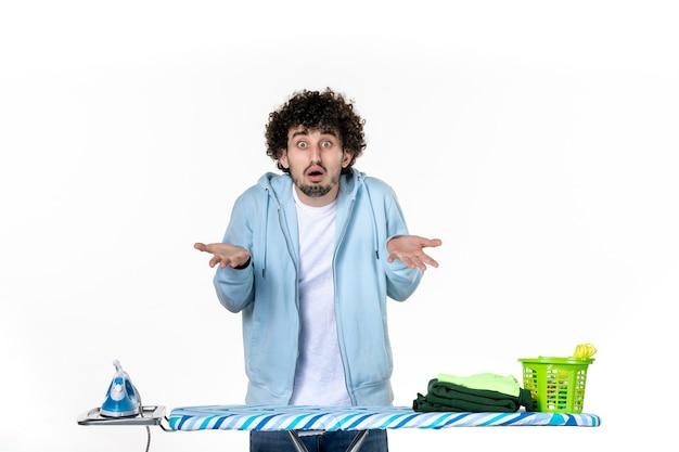 Vista frontale giovane maschio dietro asse da stiro confuso su sfondo bianco lavori domestici lavanderia colore pulizia vestiti foto ferro da stiro