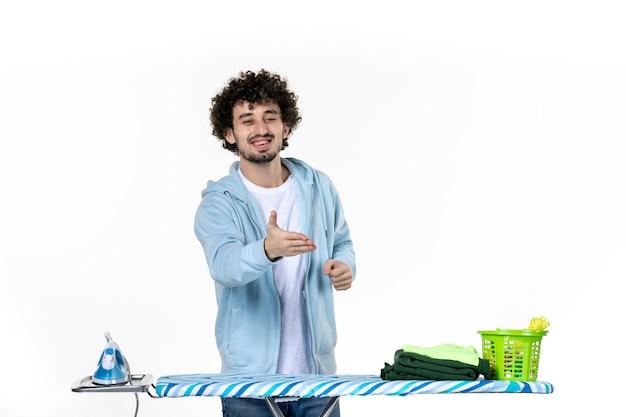 Vista frontale giovane maschio dietro l'asse da stiro salutare qualcuno su sfondo bianco vestiti uomo lavanderia foto pulizia ferro lavori domestici colore