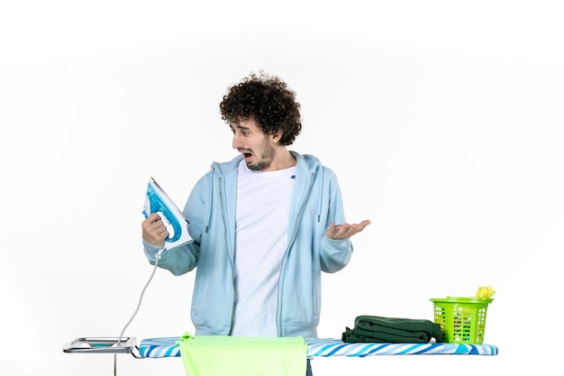 Vista frontale giovane maschio dietro asse da stiro tenendo il ferro su sfondo bianco ferro colore uomo pulizia lavori domestici lavanderia foto vestiti