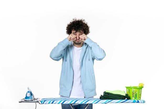 Vista frontale giovane maschio dietro l'asse da stiro imita il pianto su sfondo bianco vestiti uomo foto pulizia ferro lavori domestici colore lavanderia
