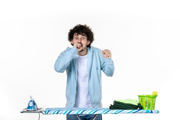 Vista frontale giovane maschio dietro asse da stiro nervoso su sfondo bianco vestiti uomo foto pulizia ferro lavori domestici colore lavanderia