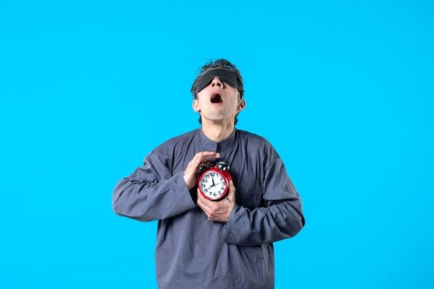 Vista frontale giovane maschio in pigiama con orologi rossi su sfondo blu incubo scuro insonnia sonno tardivo letto da sogno colori notturni