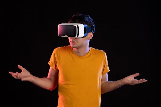 Vista frontale del giovane maschio che gioca alla realtà virtuale su giochi ad ultrasuoni scuri visual