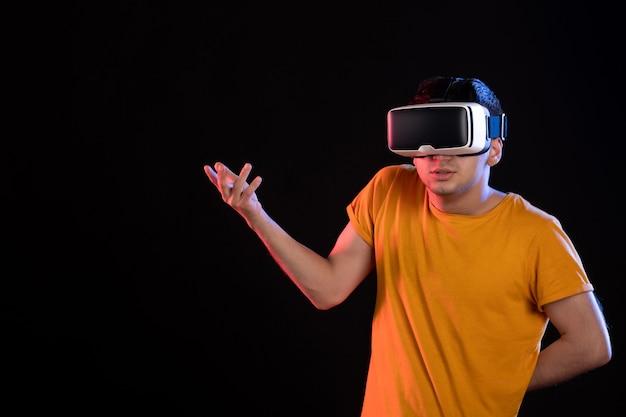 Vista frontale del giovane maschio che gioca alla realtà virtuale sul muro scuro