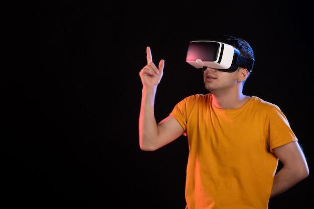 Vista frontale del giovane maschio che gioca alla realtà virtuale sul muro scuro Foto Premium
