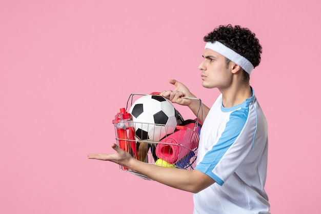 Giovane maschio di vista frontale in vestiti di sport con il canestro pieno della parete rosa di cose di sport