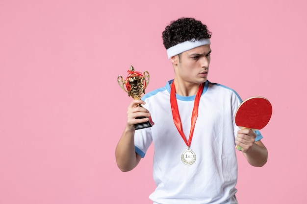 Giovane maschio di vista frontale in vestiti di sport con medaglia e coppa d'oro sulla parete rosa Foto Premium