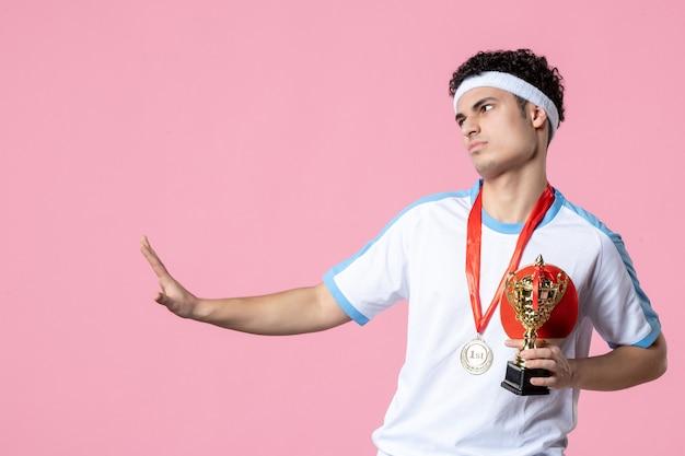 Giovane maschio di vista frontale in vestiti di sport con medaglia e coppa d'oro sulla parete rosa