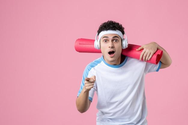 Giovane maschio di vista frontale in vestiti di sport con la stuoia di yoga sulla parete rosa