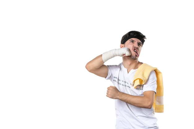 Vista frontale giovane maschio con bendaggio sulla sua mano ferita su sfondo bianco atleta palestra dieta sport dolore lesioni ospedale fit lifestyle