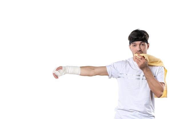 Vista frontale giovane maschio con bendaggio sulla sua mano ferita su sfondo bianco dieta sport dolore lesione corporea in forma atleta palestra ospedale