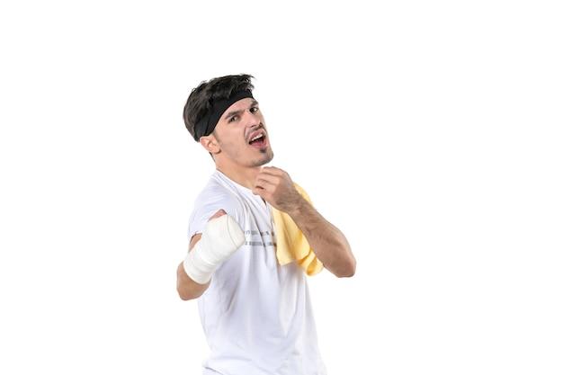 Vista frontale giovane maschio con bendaggio sulla sua mano ferita su sfondo bianco dieta sport dolore palestra stile di vita lesioni corpo in forma atleta