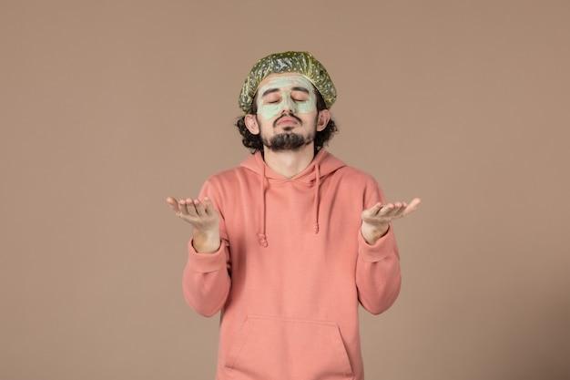 Vista frontale giovane maschio con cappuccio bouffant su sfondo marrone cura della pelle terapia della pelle capelli viso spa massaggio