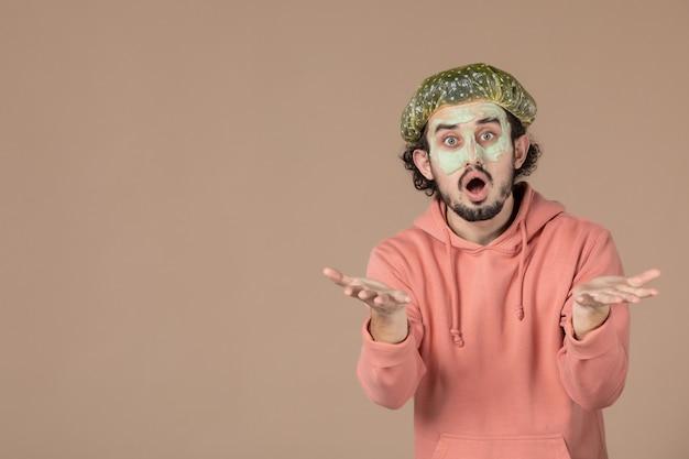 Vista frontale giovane maschio con berretto bouffant e maschera sul viso su sfondo marrone terapia dei capelli salone di cura della pelle spa pelle del viso cura del corpo