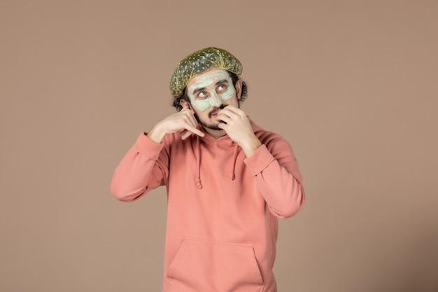 Vista frontale giovane maschio con berretto bouffant e maschera sul viso su sfondo marrone salone cura della pelle terapia della pelle capelli viso spa foto