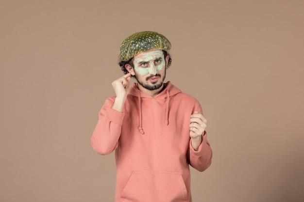 Vista frontale giovane maschio con berretto bouffant e maschera sul viso su sfondo marrone skin spa salone di cura della pelle terapia facciale