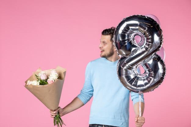Vista frontale giovane maschio con fiori e palloncini come marzo presente su sfondo rosa uguaglianza matrimonio amore orizzontale giorno delle donne sensuale date