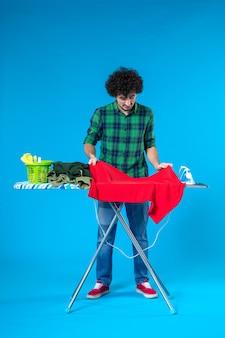 Vista frontale giovane maschio con asse da stiro piegare i vestiti su sfondo blu colore casa lavaggio lavori domestici pulizia umana