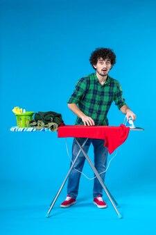 Vista frontale giovane maschio con asse da stiro piegare i vestiti su sfondo blu colore casa lavatrice pulizia umana