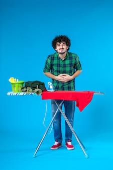 Vista frontale giovane maschio con asse da stiro avente mal di stomaco su sfondo blu pulire la lavatrice lavori domestici casa colore umano