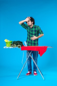 Vista frontale giovane maschio con asse da stiro avente temperatura su sfondo blu pulire lavatrice lavori domestici casa colore human