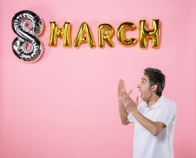 Vista frontale giovane maschio con decorazione marcia guardando da parte su sfondo rosa vacanza glamour uguaglianza festa della donna modello femminile sensuale emozione colore