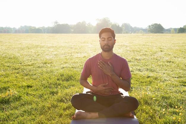 Vista frontale del giovane che medita all'aperto sul tappetino da yoga