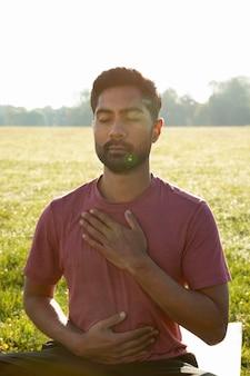 Vista frontale del giovane che medita all'aperto