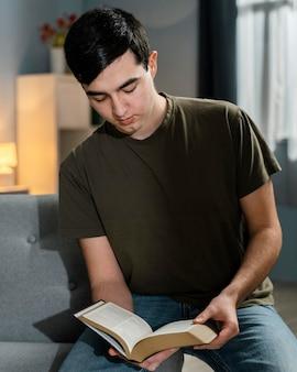 Vista frontale del giovane che legge dalla bibbia