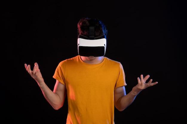 Vista frontale del giovane che indossa le cuffie da realtà virtuale sulla parete scura