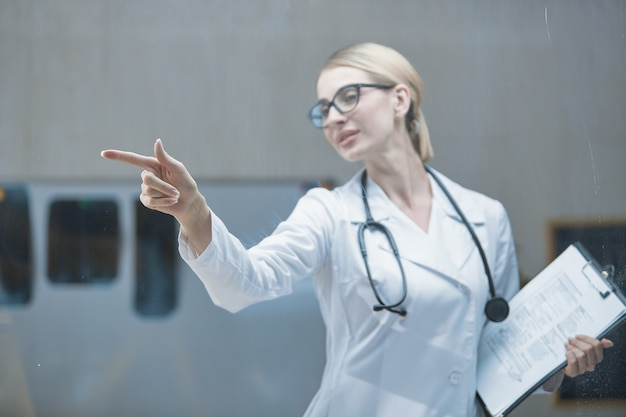Vista frontale di un giovane operatore medico con uno stetoscopio al collo che sta sviluppando un piano nel suo ufficio utilizzando un'interfaccia schermo tattile digitale il concetto di alte tecnologie