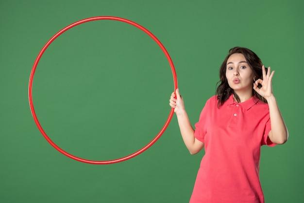 Vista frontale giovane commessa che tiene hula hoop rosso sulla parete verde yoga corpo uniforme lavoro atleta lavoro soldi shopping sale