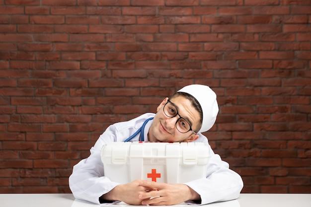 Vista frontale giovane medico sorridente in tuta medica bianca con kit di pronto soccorso sul muro di mattoni marrone
