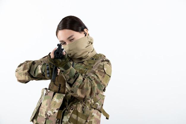 Vista frontale del giovane soldato in mimetica con mitragliatrice muro bianco