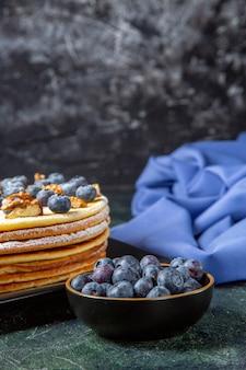 Torta di miele squisita vista frontale con mirtilli e noci all'interno della superficie scura del piatto