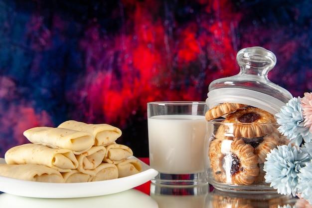 Vista frontale gustose frittelle con biscotti e latte su sfondo scuro zucchero dessert pasto biscotto torta colazione mattina colore