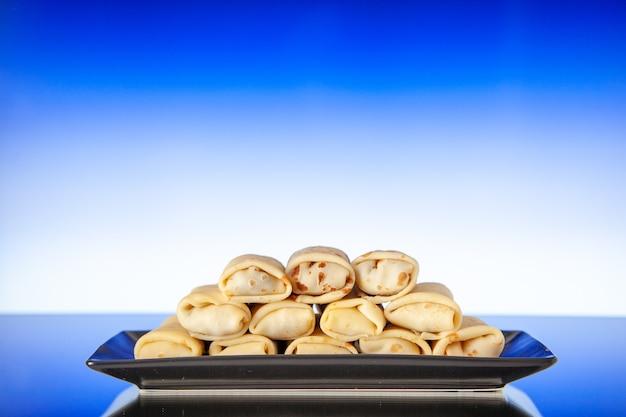 Vista frontale gustosissime frittelle arrotolate all'interno della piastra su sfondo azzurro dolce colazione mattutina dessert torta latte color zucchero