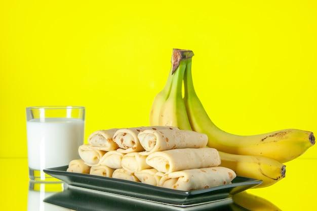 Vista frontale gustose frittelle arrotolate con banane e latte su sfondo giallo frutta dolce mattina latte dolce torta color zucchero