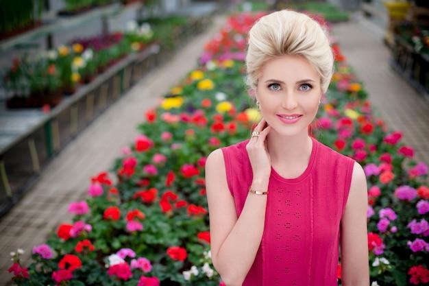 Ritratto frontale di una bella ragazza bionda con un giardino fiorito sullo sfondo