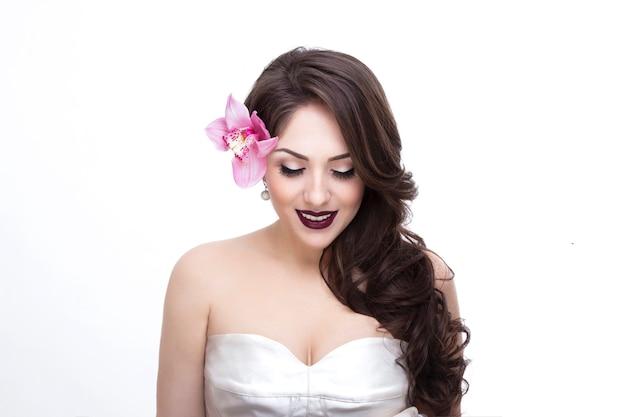 Ritratto frontale di una giovane modella con gli occhi chiusi e capelli mossi, trucco da sposa e vestito
