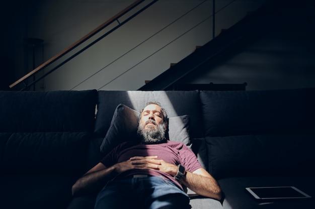 Vista frontale di un uomo barbuto sdraiato sul divano con gli occhi chiusi, illuminato da un raggio di sole in una stanza buia