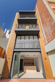Vista frontale della facciata di un edificio contemporaneo in legno e metallo con strisce verticali di travi fuori...