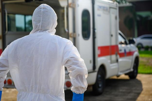 Medico in prima linea in piedi in un'ambulanza di emergenza indossare un'uniforme dpi e un'ambulanza che trasporta il corpo dei morti della malattia di coronavirus covid19