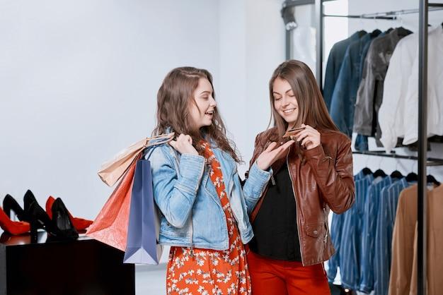 Frontview delle ragazze che comprano i vestiti durante l'acquisto al centro commerciale