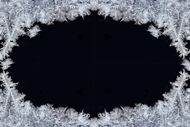 Gelo. cristalli di ghiaccio decorativi su una finestra a forma di cornice su sfondo nero opaco