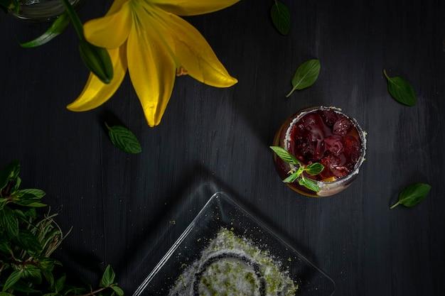 Bevanda gelata con ghiaccio e fette di limone su un tavolo grigio e un vaso con fiori gialli