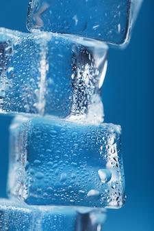 Cubetti di ghiaccio gelidi a forma di torre su sfondo blu.